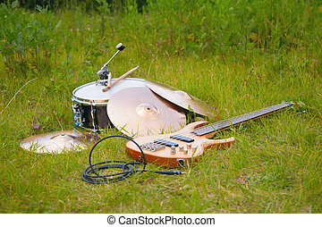 musical instruments, guitar, drum, plates on grass.