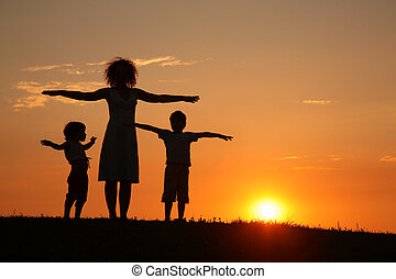 Mother and children on sunset sport training