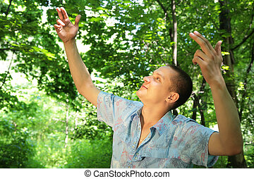 Guy in wood with rised hands like a director of birds