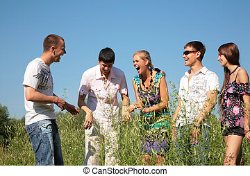 Group of five friends stands among grass