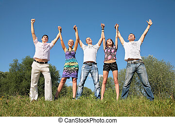 Group of friends with rised hands outdoor in summer