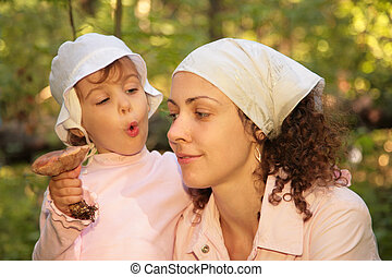 Mother and daughter with mushroom in forest