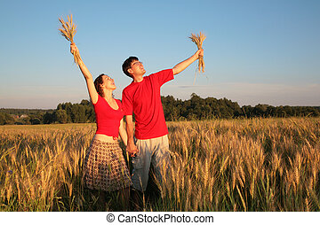 Pair in field with wheat in hands