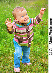 Child stands on grass