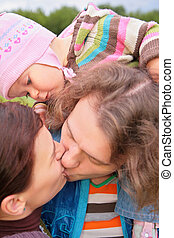 Parents with baby kiss outdoor