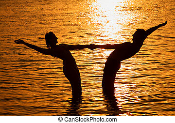 Pair keeps for hands in sea on sunset