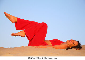Young woman in red lies on sand