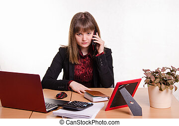 The girl behind office table talks on phone - Cute business...