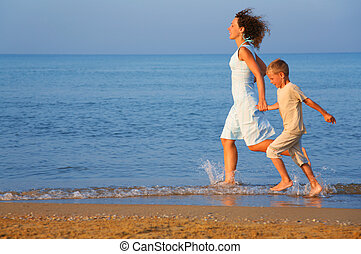 Mother with son running on edge of sea
