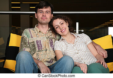 couple sit on sofa in dark hall