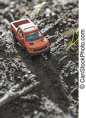 Small red off road car toy in the nature Miniature