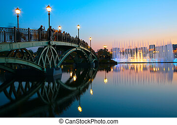 people on bridge  and fountain on sunset. Moscow.