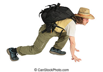 Traveller with backpack in straw hat on all fours