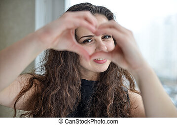 Beautiful young woman doing a heart shape with her hands