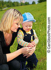 mother with child and dandelion on meadow