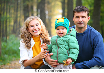 family with boy in autumnal wood