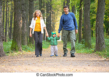 family in autumnal wood focus on child