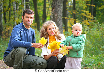 family with child in autumnal wood. focus on mother.