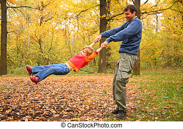 Father rotates child for hands in wood