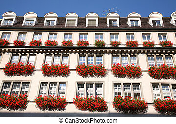Urban house with flowers on windows in Munich