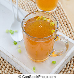 Homemade bone broth with leek in glass cup