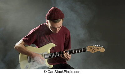 A talented musician playing guitar in a dark studio in smoke...