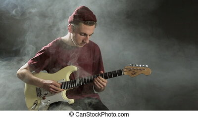Young guy playing guitar in a dark studio in smoke