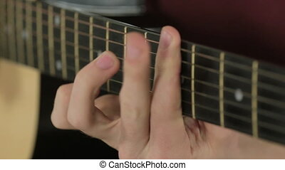 Close-up of strings on a guitar while playing - Close-up of...