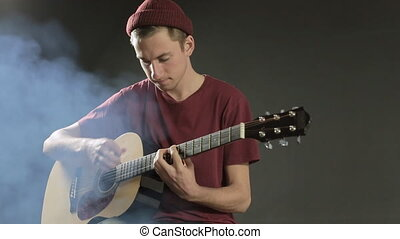 Talented young musician playing guitar in a dark studio in smoke