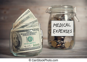 Dollars and coins in jar with medical expenses label -...