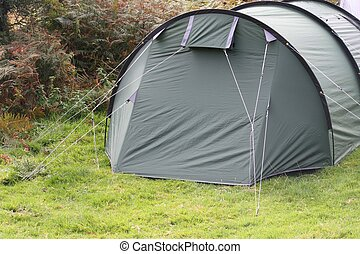 a green tent pitched on grass