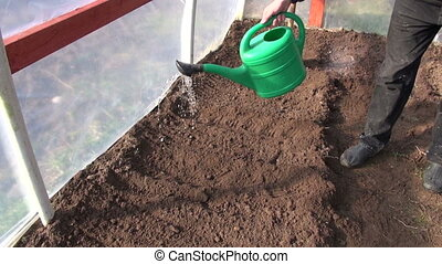 farmer watering garden bed for vegetables in spring...
