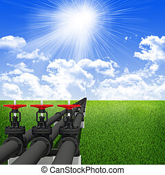 Three industrial pipes for oil transfer. Against background of blue sky , clouds, green grass