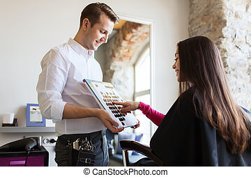 woman choosing hair color from palette at salon - beauty,...