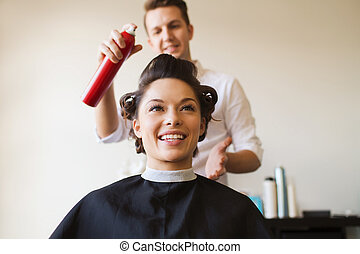 happy woman with stylist making hairdo at salon - beauty,...