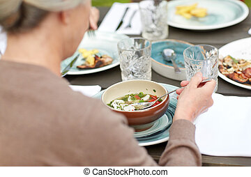 close up of woman eating soup in summer garden - family,...