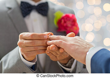 close up of male gay couple hands and wedding ring - people,...