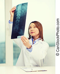 concentrated doctor looking at x-ray - healthcare, medical...