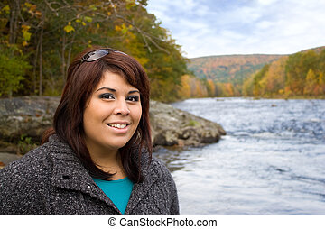 Woman In Autumn - A young plus sized model posing by a river...