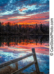 Sundown Pond and Fence - A rustic wooden fence is backed by...