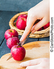 cut with a knife fresh red apples on a wooden board, fruits...