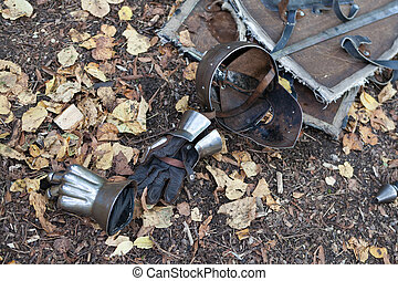 Knight armor helmet and gloves on the ground covered with...