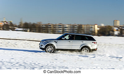 Powerful 4x4 offroader car running on snow field winter day,...