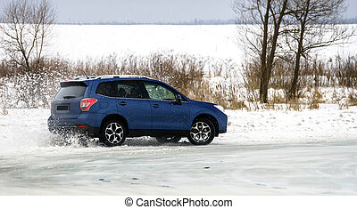 Powerful offroader car sliding by lake ice on winter sport...