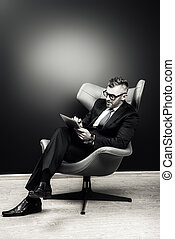 boss man - Imposing mature man in elegant suit sitting on a...