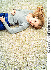 carpet - Happy girl lying on a carpet at home