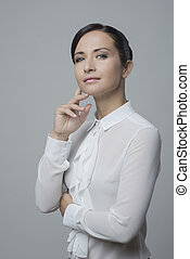 Attractive woman in white elegant shirt with hand on chin,...