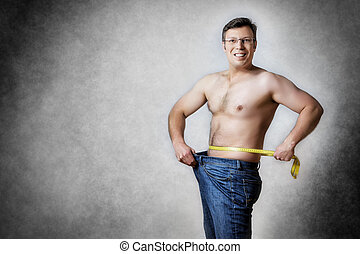 man with measuring tape - Image of a man in blue jeans with...