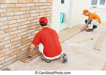 parquet workers at flooring work - Two parquet carpenter...