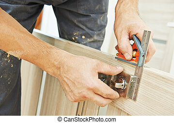door lock installation - Close-up carpenter hands with...